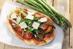 Alimento: Pizza do tomate do aspargo, do foguete e de cereja com Parmesão foto de stock royalty free