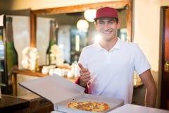 Pizza doręczeniowy mężczyzna pokazuje świeżą pizzę i aprobaty obrazy stock
