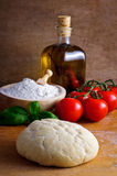 Pizza dough. Still life with pizza dough and ingredients on a wooden background Stock Photography
