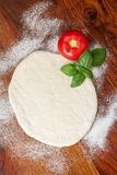 Pizza Dough. Tomato and basil on wooden table Royalty Free Stock Photo