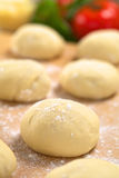 Pizza Dough. Small balls of fresh homemade pizza dough on floured wooden board with pizza ingredients (tomato, basil, grated cheese) in the back (Selective Focus Stock Photos
