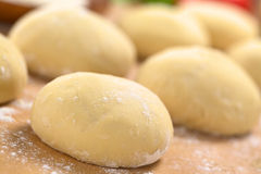 Pizza Dough. Small balls of fresh homemade pizza dough on floured wooden board (Selective Focus, Focus one third into the first pizza dough Royalty Free Stock Photo