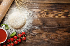 Pizza dough with ingredients on wood. Shot from above Royalty Free Stock Photography