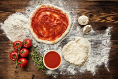 Pizza dough with ingredients on wood Royalty Free Stock Photos