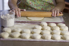 Pizza dough's. A lady flatten the dough to make flat bread pizzas using classic wooden roller Royalty Free Stock Image
