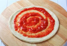 Pizza dough and tomato puree. Tomato puree spread on raw pizza dough Royalty Free Stock Photography