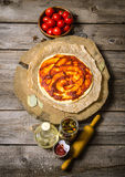 Pizza dough with tomato sauce, tomatoes, and ingrediente rolling pin for pizza. Stock Images
