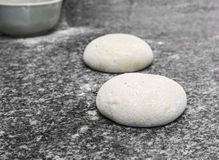 Pizza Dough. Two balls of pizza dough ready to be prepared on a table in a kitchen Royalty Free Stock Photography