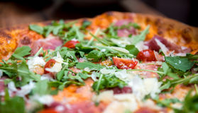 Pizza with dry cured ham and arugula Stock Images