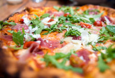 Pizza with dry cured ham and arugula Stock Photos