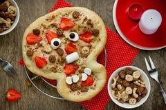 Pizza dulce bajo la forma de cráneo divertido para tratar a niños en Hallowee Foto de archivo