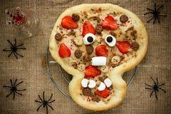 Pizza dulce bajo la forma de cráneo divertido para tratar a niños en Hallowee Fotografía de archivo
