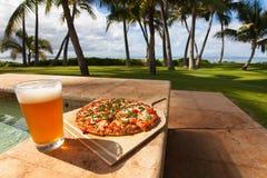 Pizza e cerveja pela piscina em Havaí Imagem de Stock Royalty Free