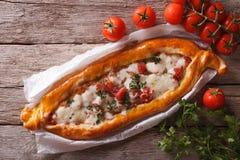 Pizza e primo piano turchi degli ingredienti su una tavola Orizzontale a Immagine Stock
