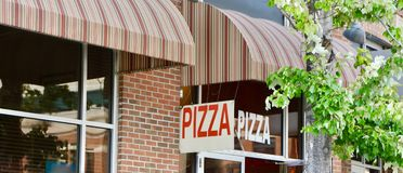 Pizza Eatery and Restaurant. A pizza shop sells handmade and homemade from scratch pepperoni, cheese, meat lovers and other popular pizza pies Royalty Free Stock Image