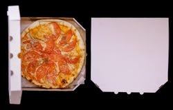 Pizza in een kartondoos tegen een donkere achtergrond Ruimte voor te stock afbeelding