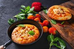 Pizza in een pan met pizza op een houten dienblad stock fotografie