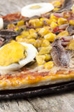 Pizza with egg and anchovy Stock Photos