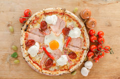 Pizza with egg, bacon, ham, sour creme, salami and pepperoni - Top view Stock Photo