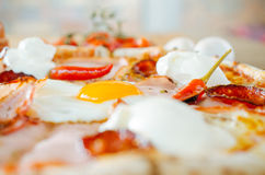 Pizza with egg, pepperoni and bacon and salami. Low angle view Royalty Free Stock Photos