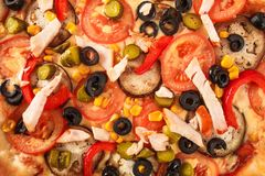 Pizza with eggplant, ham, red pepper, tomato,cucumber, olives and corn isolated on white background.  stock photography
