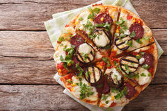 Pizza with eggplant, salami and mozzarella close up on a board. Royalty Free Stock Photos