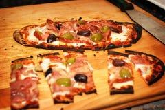 Pizza in einem hölzernen brennenden Ofen Stockbilder
