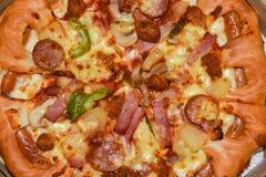 Pizza in einer Pappschachtel gegen einen hölzernen Hintergrund Pizzamenü Lebensmittelinhaltsstoffe und Gewürze für das Kochen von lizenzfreie stockfotos