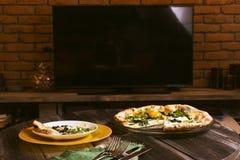Pizza en el fondo de la televisión del plasma Fondo del arte, vajilla, interior del hogar Imagen de archivo