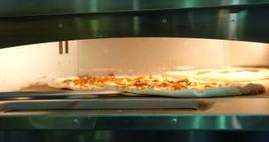 Pizza en el horno, proceso de la hornada, cocinando almacen de metraje de vídeo