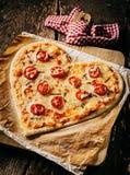 Pizza en forma de corazón cocida rematada con las rebanadas del tomate foto de archivo libre de regalías