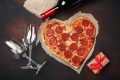 Pizza en forma de corazón con la mozzarella, sausagered, botella de vino, dos copa, caja de regalo en fondo oxidado imagen de archivo libre de regalías