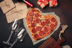 Pizza en forme de coeur avec du mozzarella, sausagered, bouteille de vin, deux verre à vin, boîte-cadeau sur le fond rouillé images stock