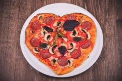Pizza en forme de coeur du plat blanc Image stock