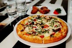 pizza en gebraden kippenvleugels Royalty-vrije Stock Afbeelding