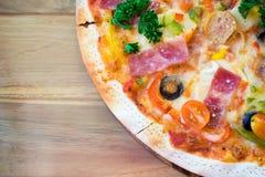 Pizza en la mesa de comedor de madera Imagenes de archivo