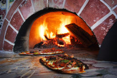 Pizza en un horno ardiente de madera Fotos de archivo libres de regalías