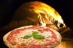 Pizza en un horno de la pizza Foto de archivo libre de regalías