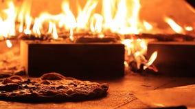 Pizza en un horno del fuego de madera almacen de metraje de vídeo