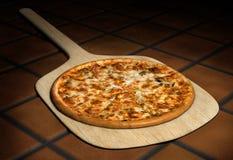 Pizza en una cáscara de madera Fotos de archivo