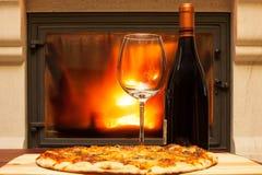 Pizza en wijn bij de open haard stock afbeelding