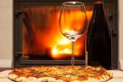 Pizza en wijn bij de open haard Royalty-vrije Stock Fotografie