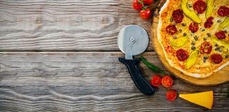 Pizza encendido por el cortador en la tabla de madera Fotos de archivo libres de regalías