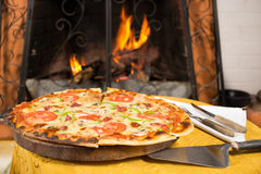 Pizza entering a wood oven Stock Photos