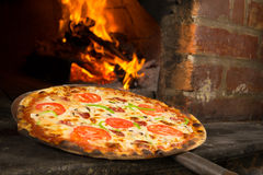 Pizza entering a wood oven Stock Image
