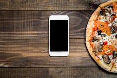Pizza, entrega italiana de la comida, llamada u orden en línea en el teléfono móvil, celular, elegante imagen de archivo