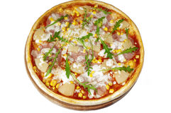 Pizza with ham, pineapples, corn  on wooden stand over wh Royalty Free Stock Images