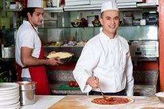 Pizza för kockbagaredanande på kök royaltyfri bild