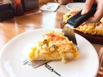 PIZZA FÖRETAG, BANGKOK, THAILAND - OKTOBER 10, 2018: En hand som förlägger ett stycke av pizza i den vita plattan Denna bild royaltyfria bilder