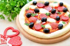 Pizza fatta a mano con salame, la mozzarella, le olive, la cipolla e la salsa al pomodoro Immagini Stock Libere da Diritti
